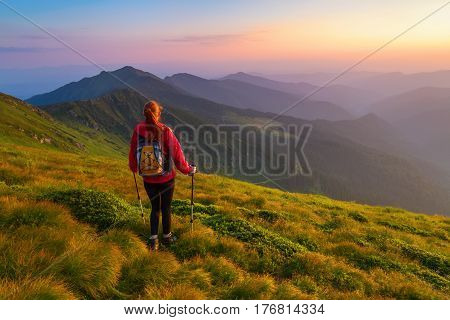 Redheaded girl athlete with a backpack and sticks stands on the green hillocks and looks at high mountain landscapes and fascinating sunset.