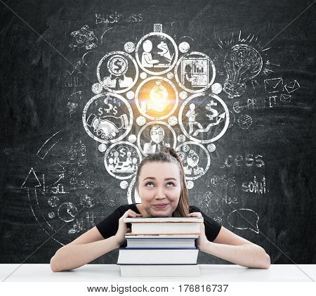 Portrait of a young businesswoman with book sitting near a blackboard with a money making idea sketch on it.