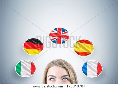 Close up of a head of a blond woman against a gray wall with five national flags drawn on it.