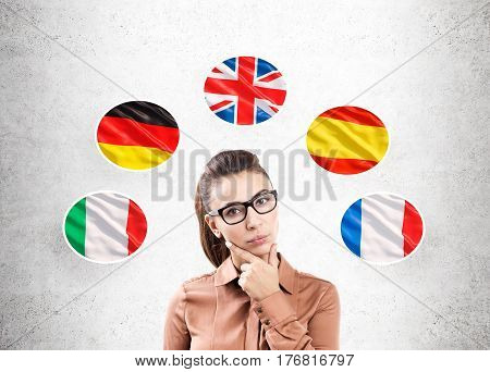 Portrait of a pensive woman in brown clothes standing near a gray wall with and five national flags around her.