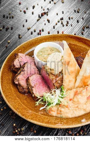 Steak on a plate with different fillings medium medium sauce with butter sauce, on a brown plate and wooden background, ebony, pita, meat lying on pita bread