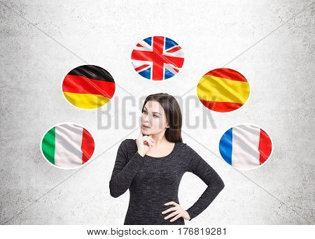 Portrait of a pensive woman in a black dress standing near a gray wall with and five national flags around her.