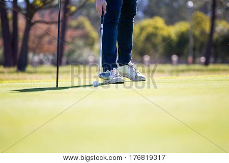 Close Up View Of A Golfer Just Pushing In A Golf Ball Into The Hole On A Green