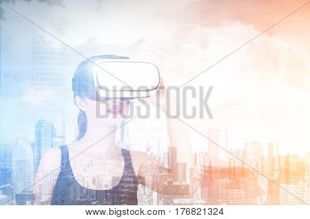 Double exposure of woman using a VR-headset while standing against a morning city panorama. Double exposure toned image mock up