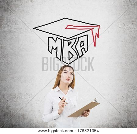 Portrait of an Asian businesswoman holding her clipboard and standing near a concrete wall with an MBA sketch on it.
