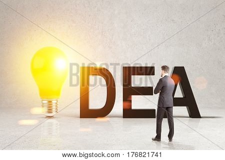 Rear view of a businessman wearing a dark suit and looking at a word idea with a large glowing light bulb instead of letter i.