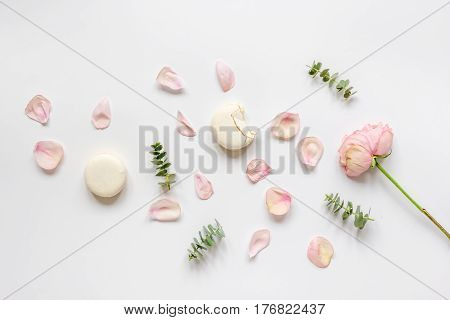 woman table flat lay with rose petals and macaroons in pastel color on white background top view mockup