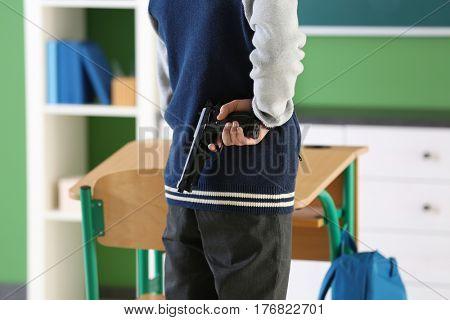 Teenage boy holding gun behind his back in classroom