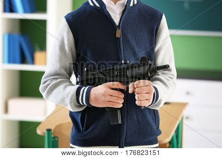 Teenage boy with gun in classroom