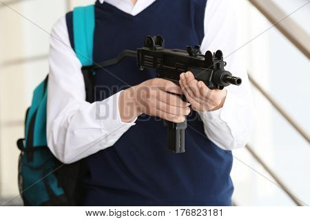 Schoolboy with machine gun in hands standing on stairs
