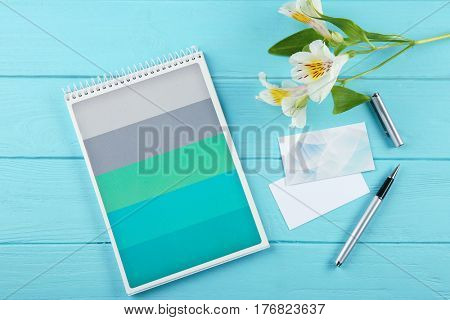 Stationery and business cards on blue wooden desk