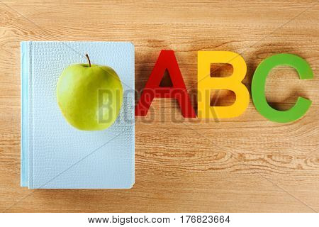 Exercise book with appetizing green apple and colorful ABC letters on wooden background