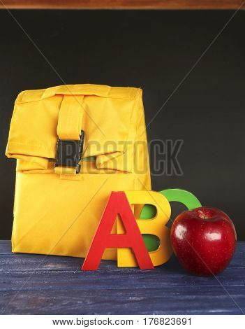 Modern lunch bag with appetizing red apple and colorful ABC letters on wooden table against blackboard background