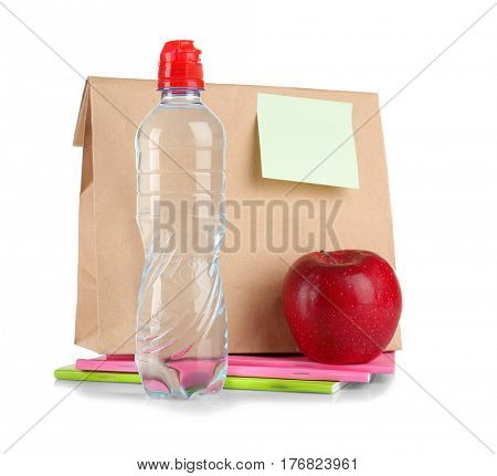 Paper lunch bag with reminder, bottle of water, apple and colorful exercise books on white background