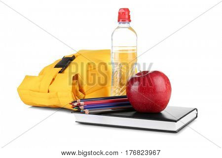 Lunch bag, bottle of water, apple and stationery on white background