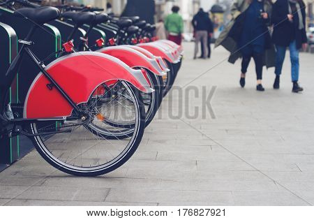 horizontal perspective view of city bike stand with row of red bicycles for rent on a city street and people passing by selective focus