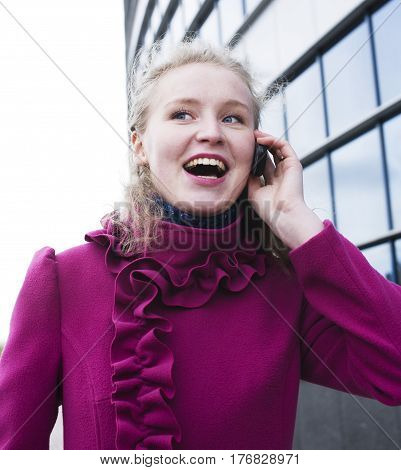 pretty blond woman talking emotional on phone outside near modern building, lifestyle people concept close up