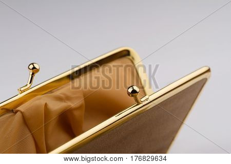 macro detail of open female cream colored vintage wallet with golden metal enclosure on grey background