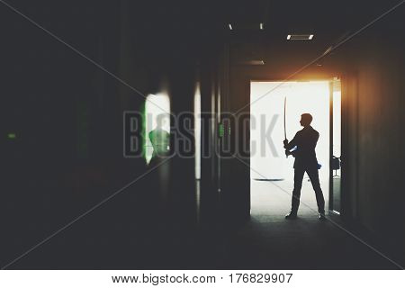 Silhouette of boss or businessman in formal suit standing in dark office corridor interior with reflections and green lights and holding katana sword like japanese samurai warrior ready to fight