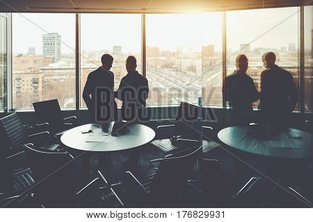 Private work meeting in office room of two business people near window with cityscape and highway outside group of businessmen watching something on screen of digital tablet in dark office interior
