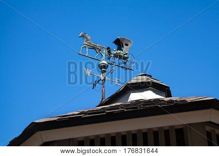 A Weather Vane which has a horse and carriage