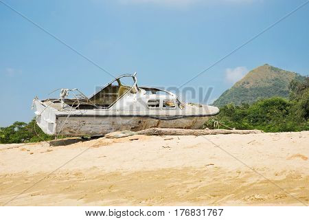 Broken yacht on the seashore. Old white boat on the sand near the sea or the ocean