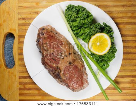 Braised beef brisket on a plate with kale and green onion set on a wooden cutting board
