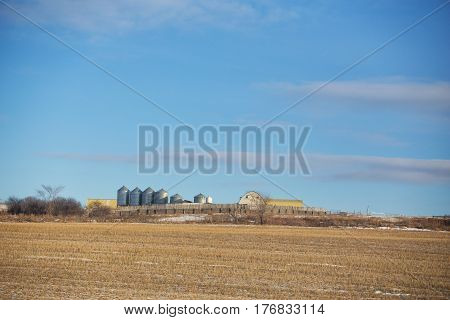 Steel grain storage bins and roof tops of buidings visible behind a long rustic wooden fence by a harvested field in a rural countryside landscape