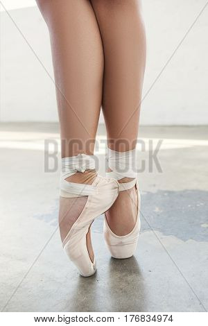 Ballerina's feet in pointe shoes over a grey background. Standing in pointe position.