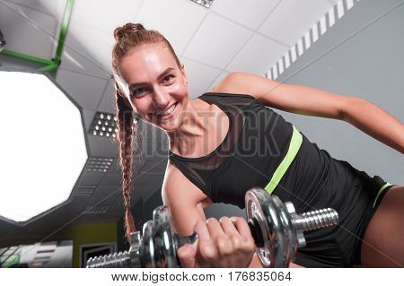 Young confident woman doing biceps curl exercise with dumbbells in fitness center. Slim girl training in the gym with dumbbells