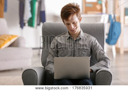 Teenager working with laptop while sitting in arm-chair at home
