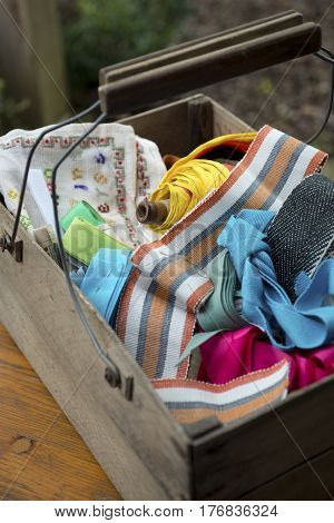 Spool Of Yarn And Fabric Ribbons In Wooden Toolbox