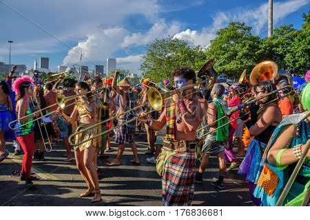 RIO DE JANEIRO, BRAZIL - FEBRUARY 28, 2017: Group of costume musicians playing trombones during Bloco Orquestra Voadora in Flamengo Park, Carnaval 2017