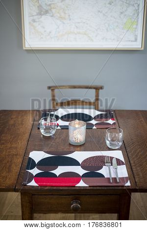Dinnerware With Lighted Candle Set On A Wooden Table