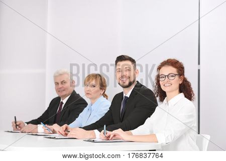 Group of four business people in elegant suits sitting at working desk in light auditorium