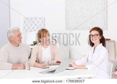 Middle aged couple discussing terms of insurance contract with agent sitting at table in office