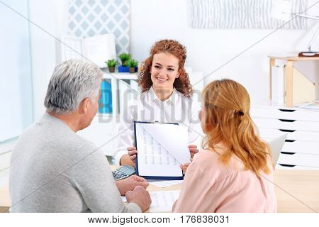 Middle aged couple signing contract at insurance agency office