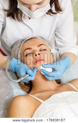 Dermabrasion girl chin. Apparatus cosmetology. Spa. Facial Rejuvenation. Mechanical peeling skin.