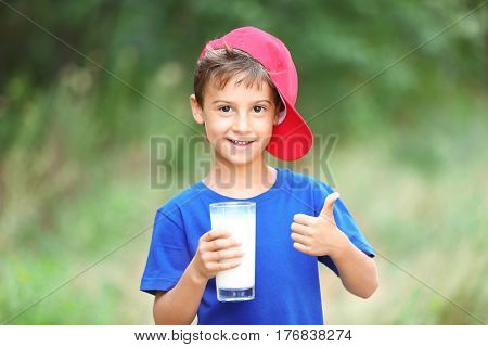 Cheerful kid in blue shirt and red hat holding glass of milk on blurred background