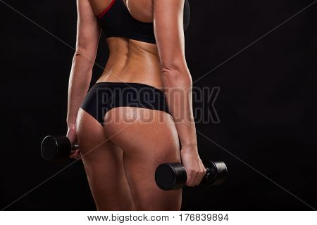 Booty of attractive athletic woman holding dumbbells, back view isolated on dark background with copyspace.