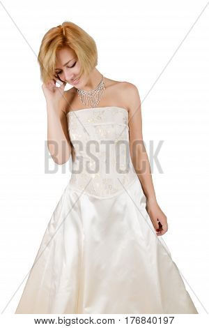 Happy girl in a white evening dress with bare shoulders and necklace talking on cell phone isolated on white background.