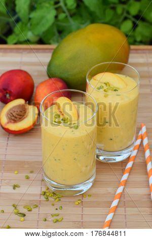 Healthy mango nectarine detox smoothie with pistachio