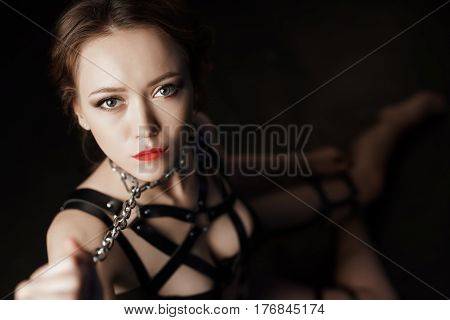 Low key portrait of beautiful dominatrix woman wearing metal chain on neck and bdsm fetish lingerie sitting on the floor at dark studio and posing to camera, shallow depth of view