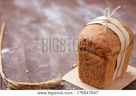 One white bread with flour on a wooden background. Advertising bread. Leaning flour. White loaf in decorative paper and rope. Brown table. Ears of wheat.
