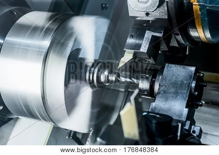 The CNC lathe drills a metal part. Abstract industrial background.