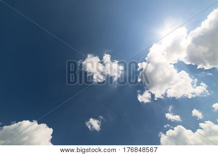 White cumulus clouds against a blue sky. Bright sunlight. Abstract background.