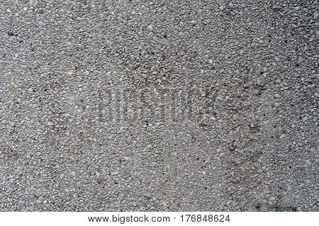 Gray concrete rough wall with protruding stones for texture or background.