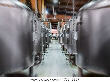 Modern Beer Factory. Rows of steel tanks for beer fermentation and maturation. Motion blur effect