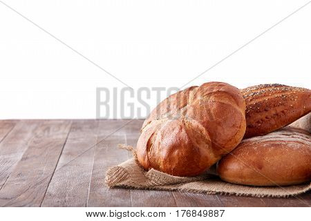 fresh healthy natural bread food group in studio on table isolated on the white background. Brown wodden table with flour. Light bread on the cloth linen. Natural materials and products.