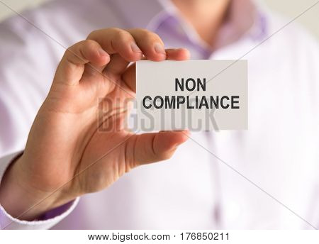 Businessman Holding A Card With Non Compliance Message